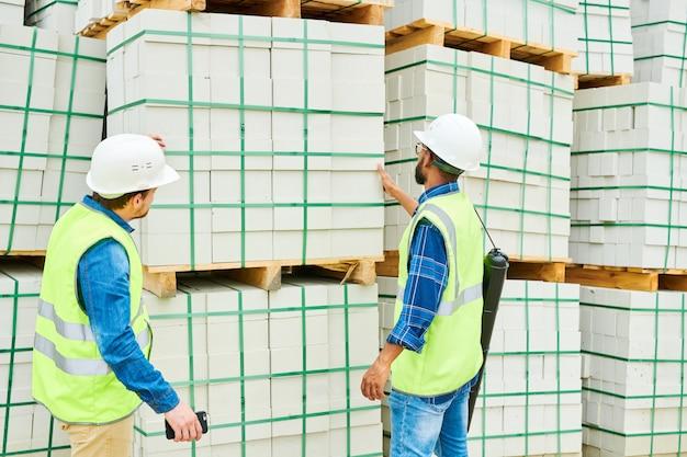 Anonieme bouwinspecteurs die naar materialen kijken