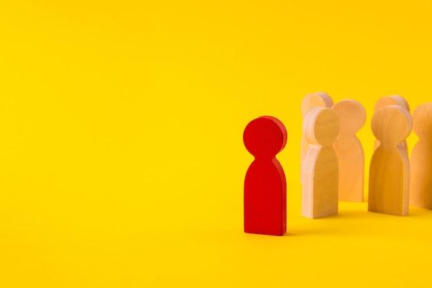 Anonieme houten figuren van mensen die gemeenschap verzamelen en hun leider volgen