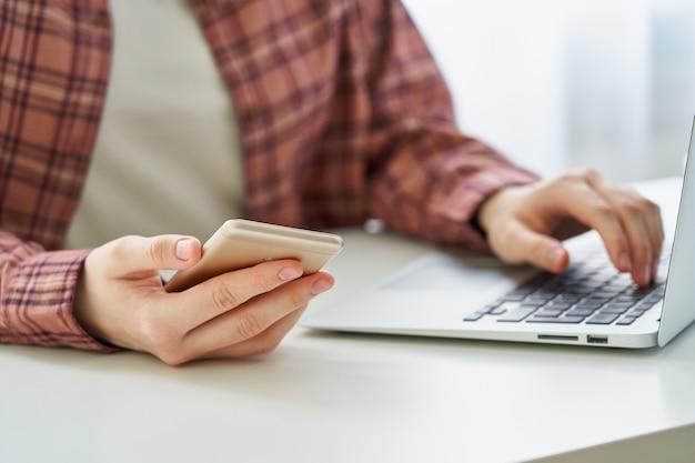 Anonieme jonge vrouwelijke browsen smartphone tijdens het typen op laptop millennial data privacy concept