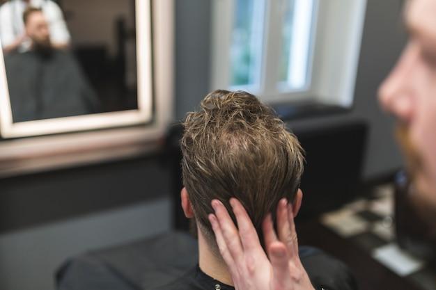 Anonieme kapper die mousse op haar van de mens toepast