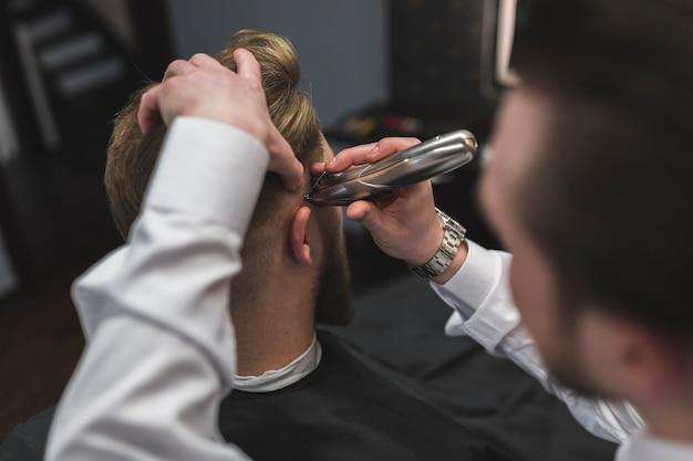 Anonieme kapper scheerhaar van klant met trimmer
