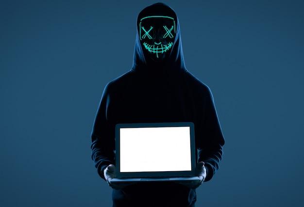 Anonieme man in een zwarte hoodie en neon masker hacken van een computer