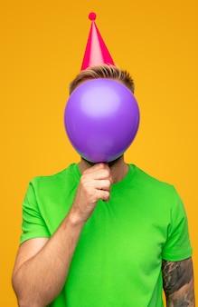 Anonieme man in feestmuts die gezicht bedekt met ballon