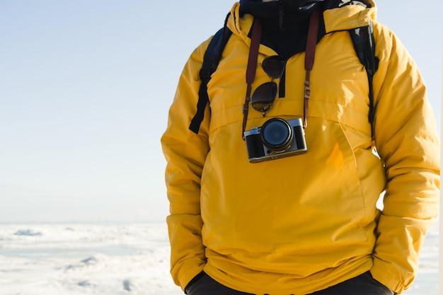 Anonieme man in gele regenjas met rugzak en camera op natuurlijke bevroren zee