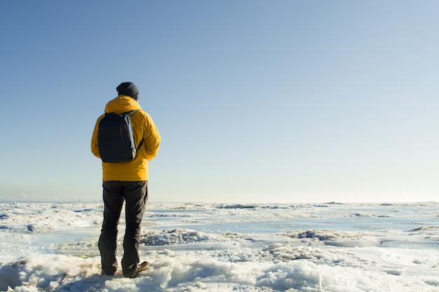 Anonieme man in gele regenjas met rugzak staan en kijken op bevroren zee