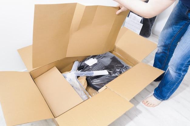 Anonieme man in spijkerbroek thuis en doos opent met nieuwe bureaustoel voor montage