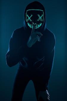 Anonieme man in zwarte hoodie die zijn gezicht verbergt achter een neonmasker