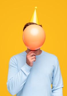 Anonieme man verbergt gezicht achter ballon
