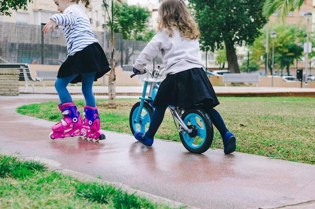 Anonieme meisjes met fiets en rolschaatsen