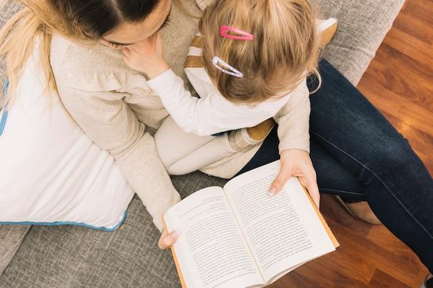 Anonieme moeder en dochter lezen op de bank