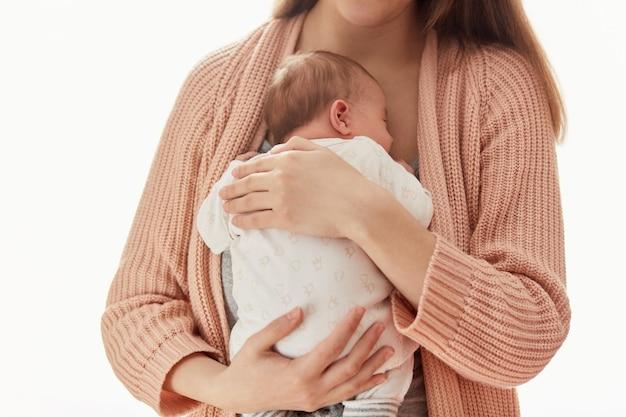 Anonieme moeder houdt haar pasgeboren baby in haar armen. familieportret van vrouw met kind, dame die warm vest draagt dat haar kind koestert en liefde uitdrukt, poseren geïsoleerd op witte achtergrond.