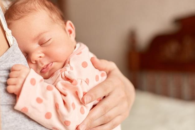 Anonieme moeder met schattige kleine baby in handen poseren indoor, charmante baby slapen in mama's armen, kind jurken slaper met noppen, familie, moederschap, jeugd.