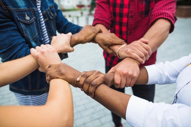 Anonieme multiraciale mensen stapelen handen