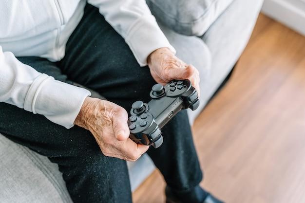 Anonieme oude oudere vrouw bijsnijden die thuis een videogame speelt