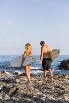 Anonieme paar met surfplanken lopen op rotsachtige kust