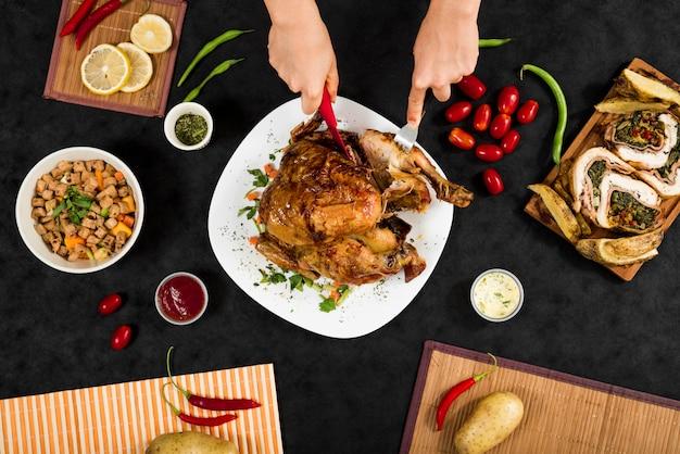 Anonieme persoon die kip voor diner snijdt