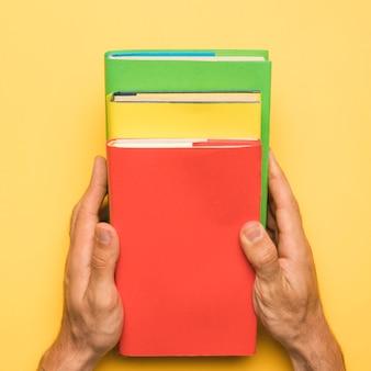 Anonieme persoon die kleurrijke boeken op gele achtergrond houdt