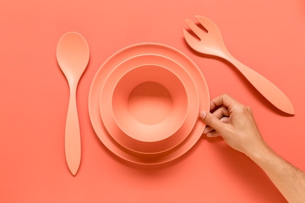Anonieme persoon die roze vaatwerk op tafel zet