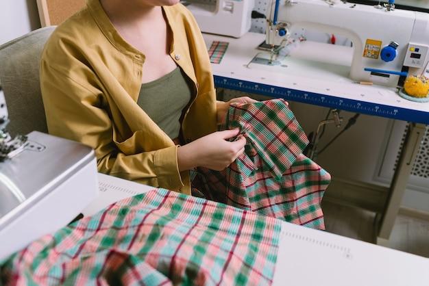 Anonieme portret van vrouwelijke kleermaker die in haar atelier werkt
