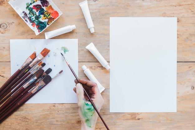 Anonieme schilder holding penseel en tekening op papier