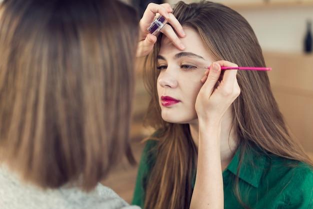Anonieme stilist die eyeliner op model toepast