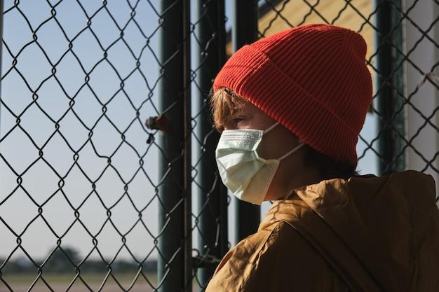 Anonieme tiener die door de omheining van de kettingsverbinding in zonlicht kijkt
