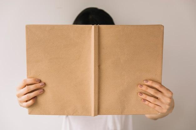 Anonieme vrouw die boekdekking toont aan camera