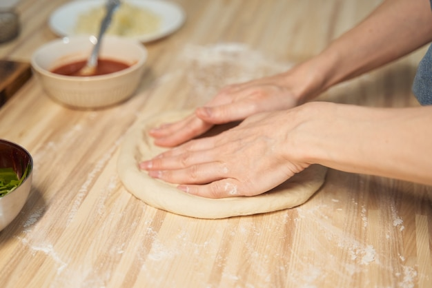 Anonieme vrouw die deeg op keukentafel thuis, appartement kneedt. zelfgemaakt eten
