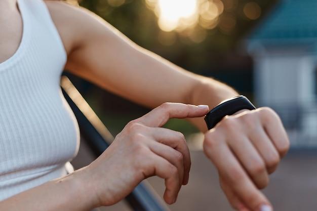 Anonieme vrouw die een draagbaar apparaat voor fitness en gezondheid controleert op haar hand, onbekende vrouw in witte top poseren buiten in het stadion bij zonsondergang.