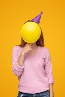 Anonieme vrouw die gezicht bedekt met verjaardagsballon