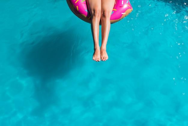 Anonieme vrouw die op opblaasbare ring zwemt