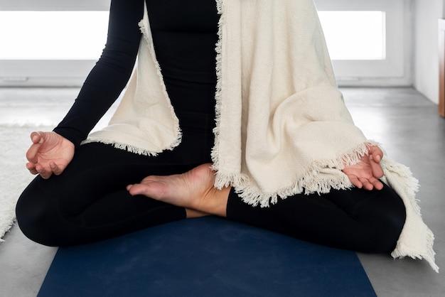 Anonieme vrouw in activewear en sjaal mediteren in lotus houding met mudra gebaar tijdens yoga thuis