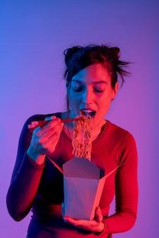 Anonieme vrouw met aziatische noedels doos voor lunch met stokjes in studio met blauwe en rode lichten