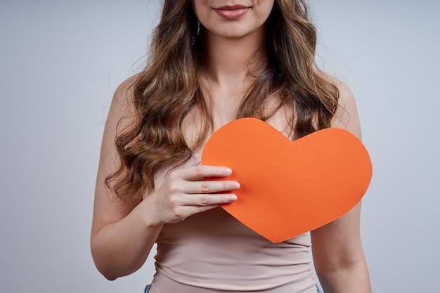 Anonieme vrouw met een hart van papier op haar borst, kijkend naar de camera, op een grijze achtergrond. fijne valentijnsdag. wereldhartdag.