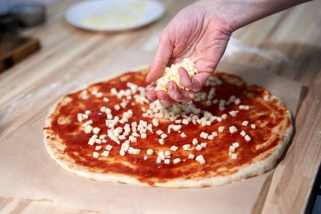 Anonieme vrouw topping rustieke italiaanse zelfgemaakte pizza deeg margherita. zelfgemaakt eten