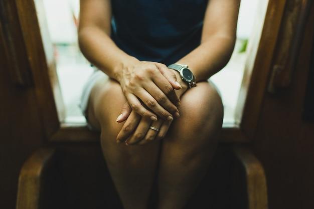 Anonieme vrouw zittend op een trap denken en nadenken bezorgd in eenzaamheid, toegevoegde graankorrel.