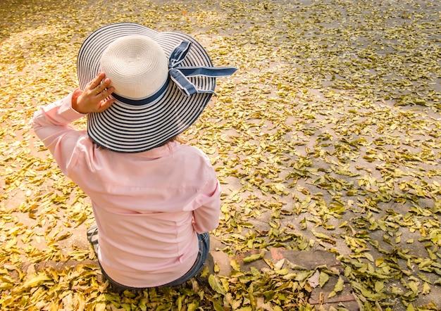 Anonieme vrouwen met blauwe hoeden zitten alleen. leun achterover en geniet in het park vol bladeren over de grond.