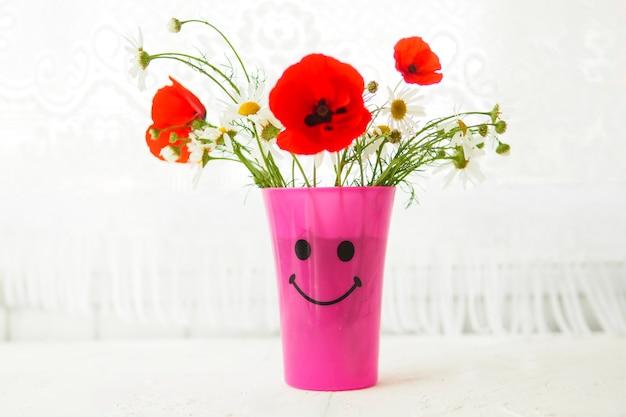 Ansichtkaart een boeket madeliefjes en klaprozen in een roze vaas met een beschilderde snuit op de tafel bij het raam.