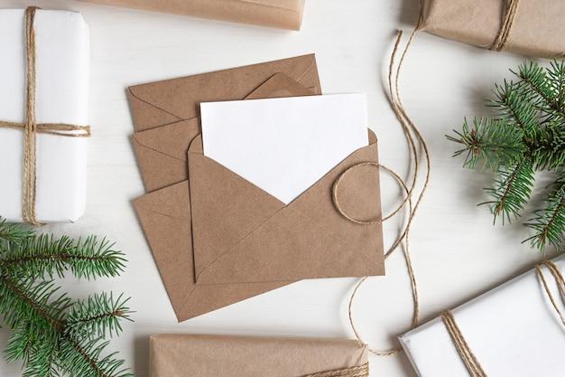 Ansichtkaart in een ambachtelijke envelop op een houten witte tafel met geschenken mock-up voor kerstbrief
