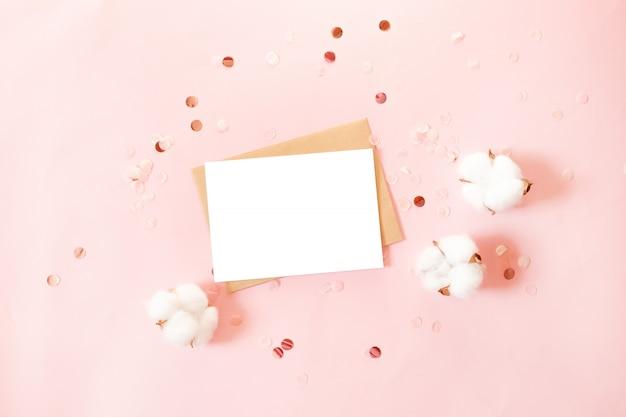 Ansichtkaart met ambachtelijke papieren envelop, glitter decor en katoen bloemen op roze achtergrond