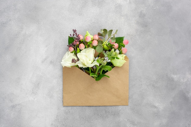 Ansichtkaart met open envelop van kraftpapier gevuld met lentebloemen