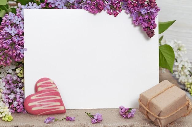 Ansichtkaart met witte envelop en bloemen van lila, ambachtelijke doos cadeau op houten tafel.