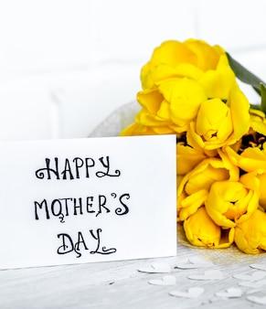 Ansichtkaart moederdag en gele tulpen op een lichte houten achtergrond, concept vakantie