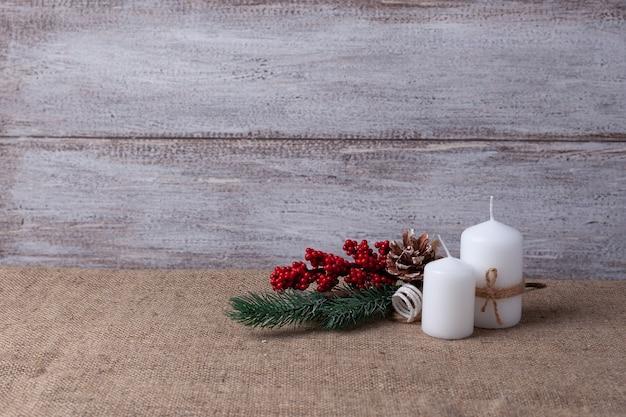 Ansichtkaart van twee witte kaarsen en een kerstboomtak op een houten