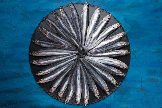 Ansjovis in de vorm van een cirkel op een zwarte steen. seafood. kleine zeevis
