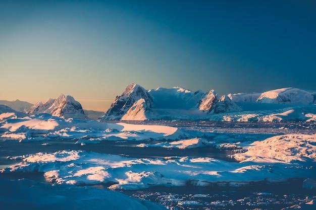 Antarctisch landschap met besneeuwde bergen tegen het warme licht van de blauwe hemelzonsondergang op de berg