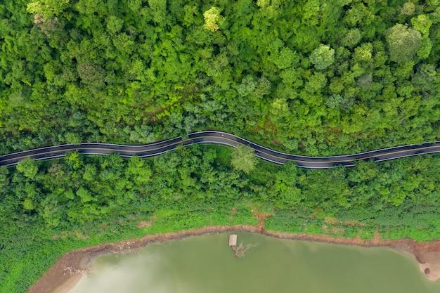 Antenne boven weergave groene bergbos en rivier in het regenseizoen en gebogen weg op de heuvel verbinden platteland