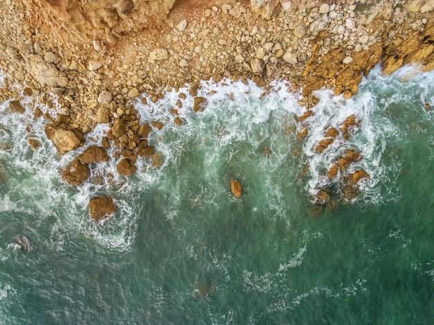 Antenne. golven sloegen tegen de kust, het uitzicht vanuit de lucht.