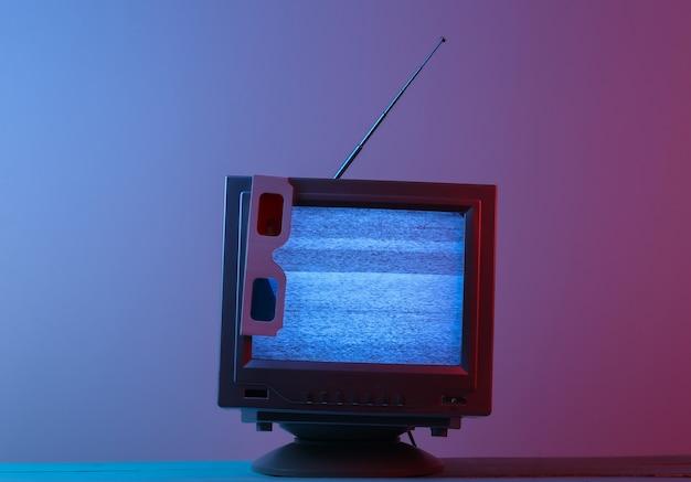 Antenne ouderwetse retro tv-ontvanger met anaglyph stereobril in roze blauw gradiënt neonlicht