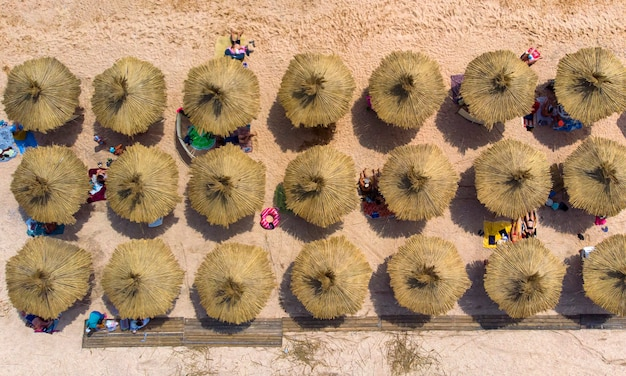 Antenne. rieten parasols op het strand aan zee. bovenaanzicht van drone.